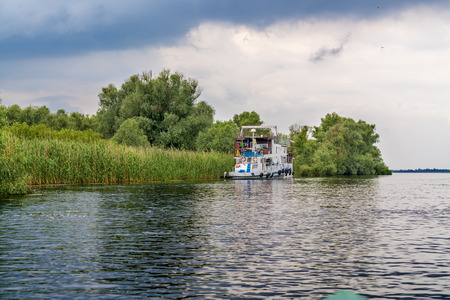 swampy: Boat with tourists sailing in the Danube Delta, Romania