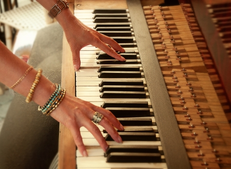 woman with rings and bracelets plays the piano photo