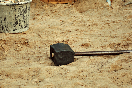 large construction hammer on the sand at a construction site photo