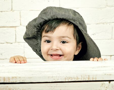protruding eyes: small child wearing a cap hiding behind a white wooden box