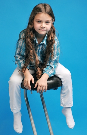 no teeth smile: white caucasian little girl on a bar stool with long hair thought Stock Photo