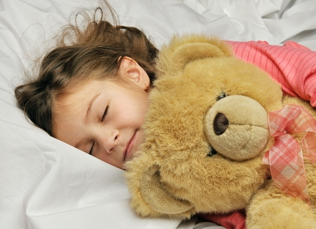 girl sleeping with a toy bear on a white bed photo