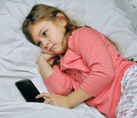 questioned: girl in bed waiting for a call on the phone Stock Photo