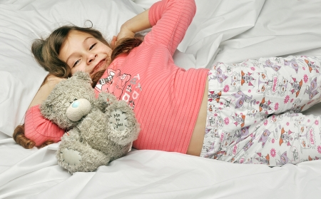 Girl wakes up with a toy bear on a white bed photo