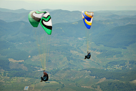 two paragliders flying over the mountains in Spain