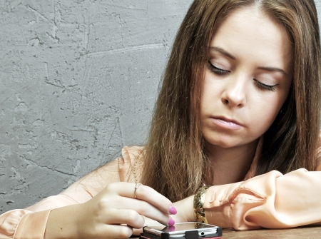 afloat: young girl at the table looking at mobile phone Stock Photo