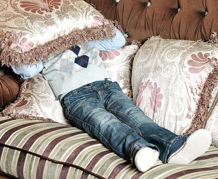 conversational: boy is lying on the couch and buries his face in the pillow