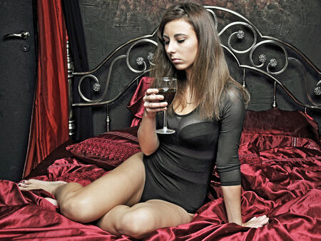erotically: sad girl in a body with a glass of wine in bed