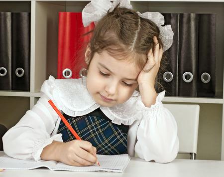 girl in school uniform doing school work photo