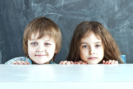 Boy and girl hiding behind a table near the school board photo