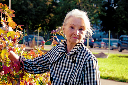 parkinson's disease: elderly woman with Parkinsons disease for a walk in the autumn