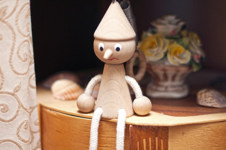 Wodden toy sits on a shelf at home photo
