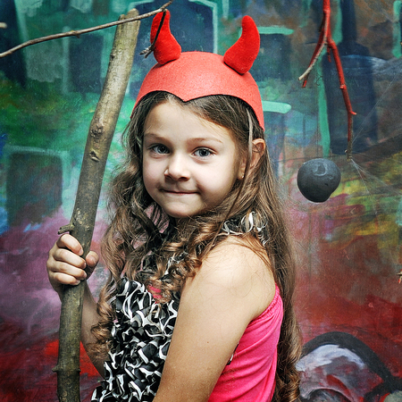 beautiful little girl in the red cap with horns on Halloween photo