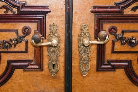 doorhandle: old metal door-handle on a wooden door Stock Photo