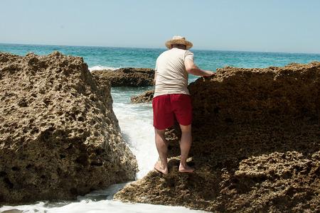 climbed: man climbed on a rock in the sea