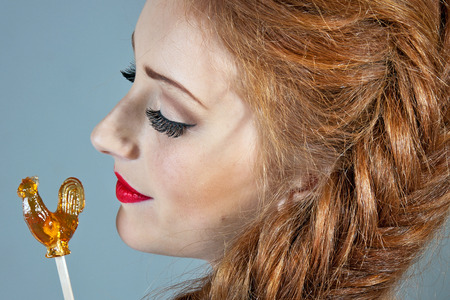 Beauty woman. Beautiful model girl with with a lollipop - Cockerel photo
