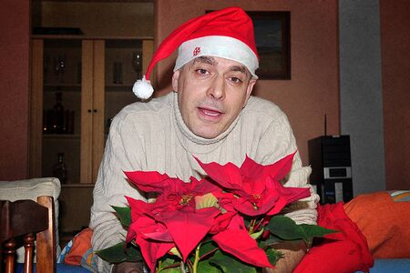 average age: Spanish man in santa hat at Christmas in the house