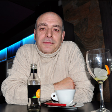 average age: Spanish man sitting at a table with a cup of coffee at home