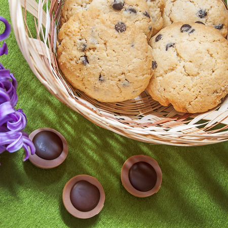 underlying: hyacinth, cookies, candy and wicker basket on a green background