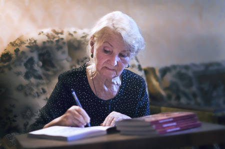 grandaughter: elderly woman writing at a table in his apartment