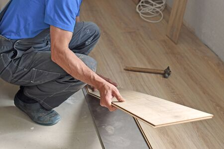 substrate: male carpenter puts the laminate in the room