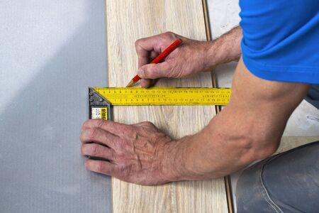 wood laminate flooring: hands of a carpenter measuring wood laminate flooring Stock Photo
