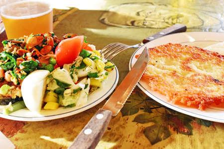 papas doradas: salad and hash Browns on a wooden table Foto de archivo