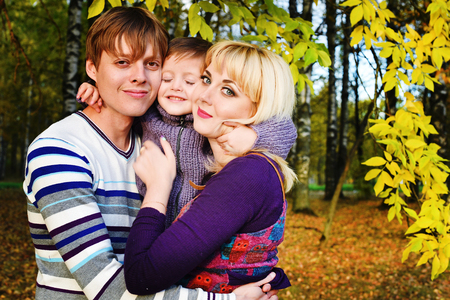 happy family nature: Picture of lovely family in Autumn Park, happy young parents with nice adorable son playing outdoors Stock Photo