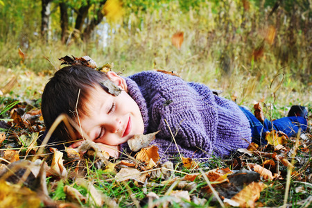 fun day: happy boy lying on leaves in autumn Park