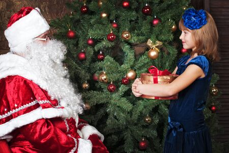 receives: happy girl receives a gift from Santa Claus