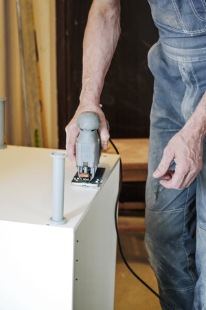 carpenter's sawdust: carpenter works with an electric jigsaw