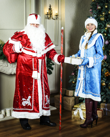 snegurochka: Russian Christmas characters: Ded Moroz (father Frost) and Snegurochka (snow girl) around the Christmas tree Stock Photo