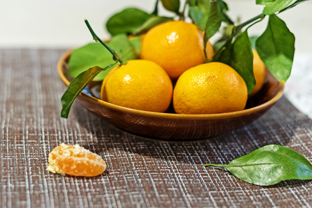 Tangerines (oranges, tangerines, clementines, citrus) with leaves in a ceramic plate Stock Photo