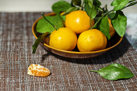Tangerines (oranges, tangerines, clementines, citrus) with leaves in a ceramic plate Archivio Fotografico - 115544699
