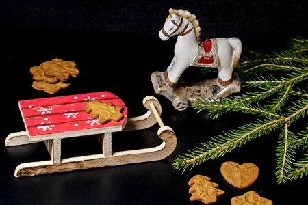 Wooden sleigh and toy horse with Christmas tree branch and Christmas cookies on black background Banque d'images