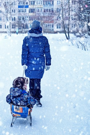 Happy mom rolls her son on a sled. Beautiful, romantic atmosphere on a snowy winter day. The concept of relationships.