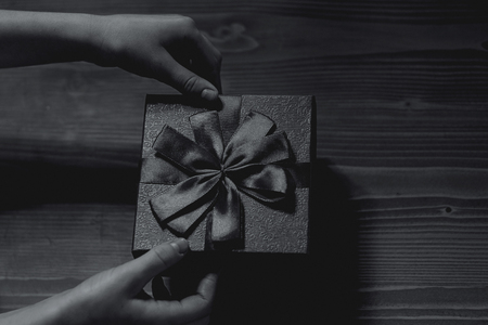 gift untiechildrens hands untie the bow on the gift box on wooden background, top view. black-white Stock Photo