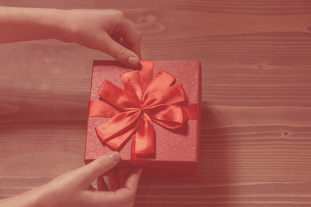 gift untiechildrens hands untie the bow on the gift box on wooden background, top view. gradient background. Stock Photo