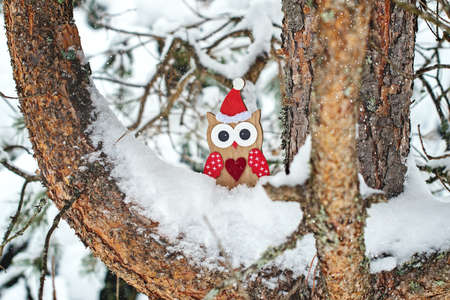 wooden owl toy in Santa costume on snow-covered pine tree.