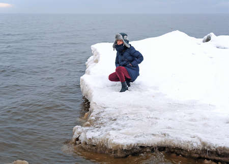 woman standing on the snowy shore of the Baltic Sea.