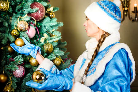 Russian Christmas characters: Snegurochka snow girl around the Christmas tree.