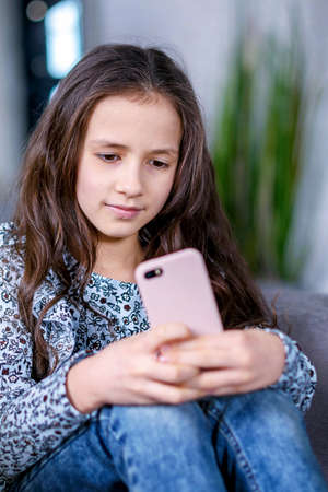 Happy teenage girl checks social networks while holding a smartphone in her hands. A young schoolgirl uses a mobile phone app to play games, correspond with friends, and relax on the couch.