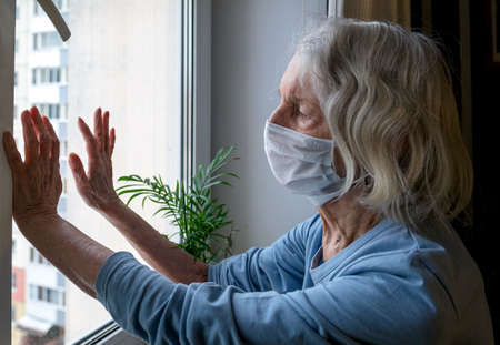 Lonely old woman in a medical mask looks out the window during the lockdown. A depressed lady at home during the covid-19 pandemic.