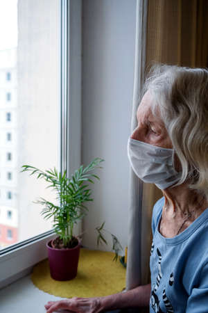 Lonely old woman in a medical mask looks out the window during the lockdown. A depressed lady at home during the covid-19 pandemic