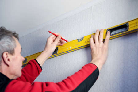 Construction tool bubble alcohol level in the hands of a man. Marking the wall. Working at home during the pandemic. Stock Photo