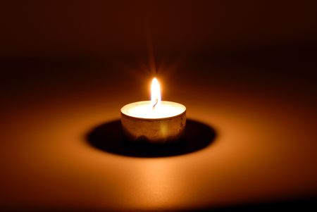 artificial lights: Small flame of a burning candle in darkness Stock Photo