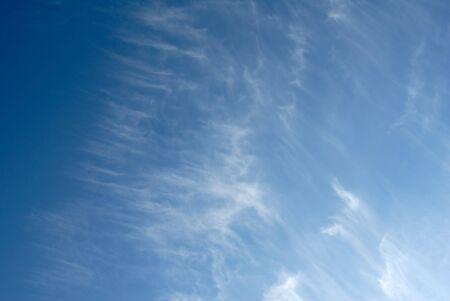 lingering: Lingering white clouds in the dark blue sky