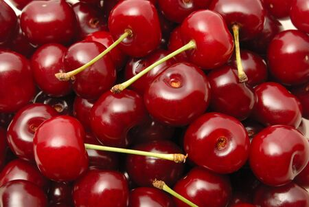 Background from a red cherry with green fruit steams Stock Photo