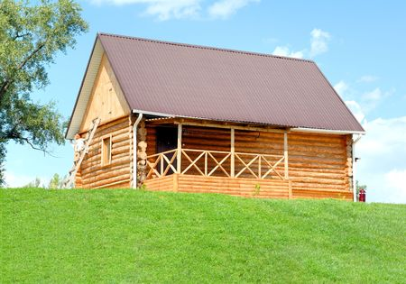 The wooden house with a lawn on a background of the blue sky Stock Photo - 3385938