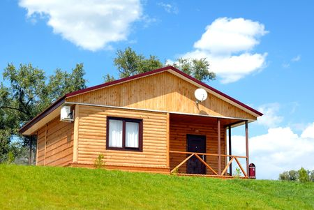The wooden house with a lawn on a background of the blue sky Stock Photo - 3628928